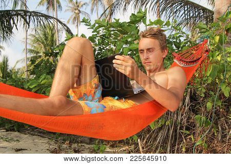 Young Smiling Man Lies In Hammock Outdoors. Freelance
