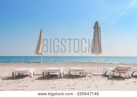 Summer Rest On Sea Beach Background. Deckchair Or Sunbeds With Umbrellas On White Sand Of Resort Bea