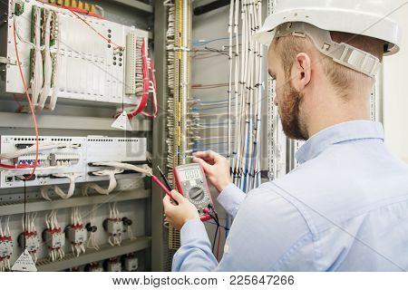 Service Man With Multimeter In Hands Adjusts Electric Control Panel. Engineer In Helmet Tests Device