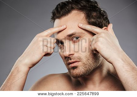 Close up portrait of a young shirtless man squeezing pimple on his face isolated over gray background