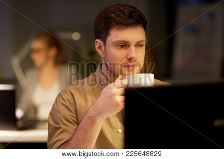 business, deadline and technology concept - man with computer working and drinking coffee at night office