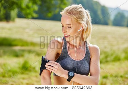 Young woman with fitness tracker and mp3 player training in summer