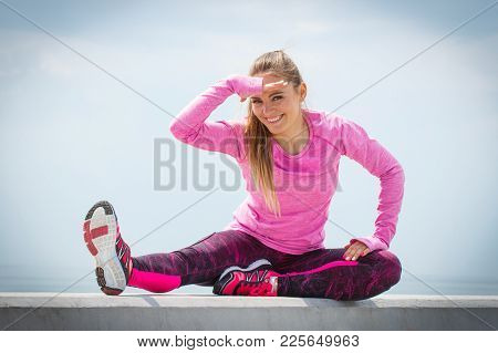 Slim Sporty Girl Wearing Sporty Clothes, Looking Into Distance By The Sea And Exercising Or Stretchi