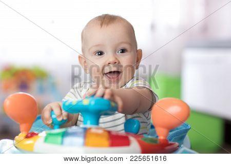 Portrait Of Baby Boy Playing In Baby Walker