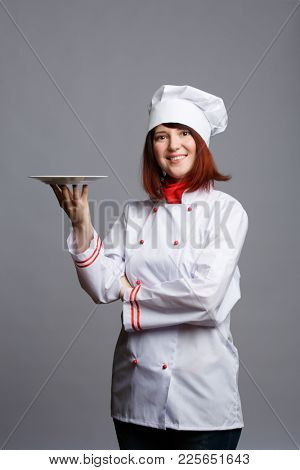 Photo of brunette chef in white robe and cap with empty plate in hand