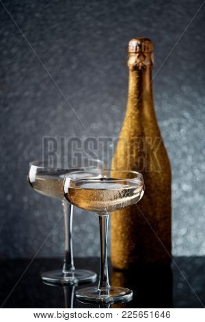Photo of bottle of sparkling wine in gold wrapper with two wine glasses
