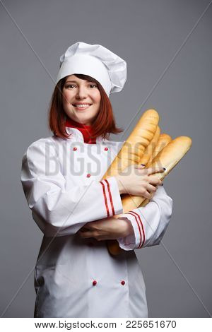 Photo of brunette chef in white robe and cap with loaves in hand on empty gray background