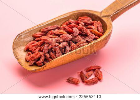 rustic wooden scoop of dried red Tibetan goji berries (wolfberry) - superfruit