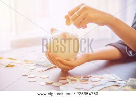 Coins On Hand Are Dropped Piggy Bank With Cash Pile On Wooden Top Table, Money Savings Concept.