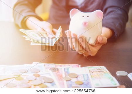 Piggy Bank In Hand With Cash Pile On Wooden Top Table, Money Savings Concept.