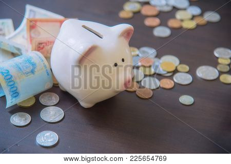 Piggy Bank With Cash Pile On Wooden Top Table, Money Savings Concept