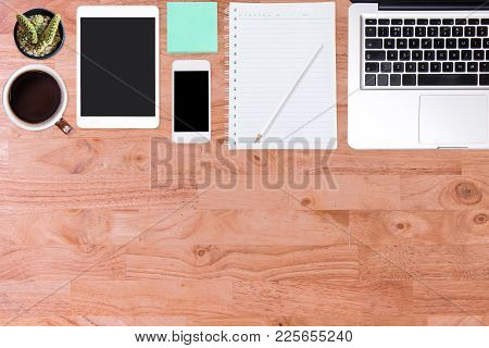 Wooden Office Desk Table With Laptop Computer, Smartphone, Notebook And Cup Of Coffee. Top View With