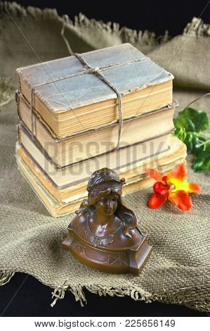 Old Books, A Flower And A Bronze Bust On The Table. Still Life, Object, Exterior