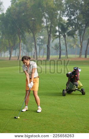 Vietnamese Mature Woman Ejoying Playing Golf Alone