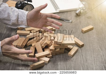 Insolvency Of Executive Placing Wood Block On The Tower Game. Concept Business Bankruptcy.