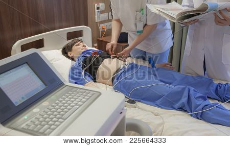 A Nurse Is Fixing Cardiograph Sensors On A Young Female Patient In Modern Hospital.