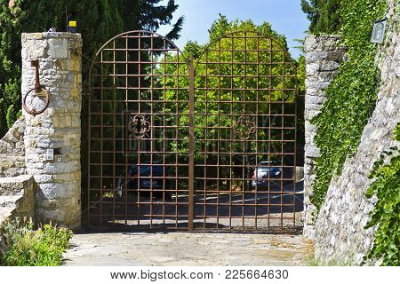 Typical Tuscan Steel Gate With Intercom And Alarm System. Automatic Gate In Front Of The Driveway In