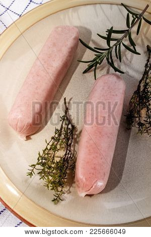 Home Made Raw British Sausages With Herbs On A Plate