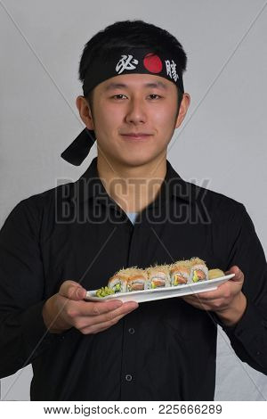 Asian cook hold a sushi roll dish wearing a black bandana with Chinese word ( victory )