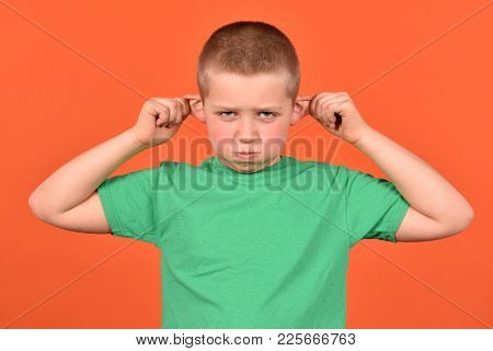 Not Obedient Boy. A Bad Mood. A Young Man On An Orange Background.