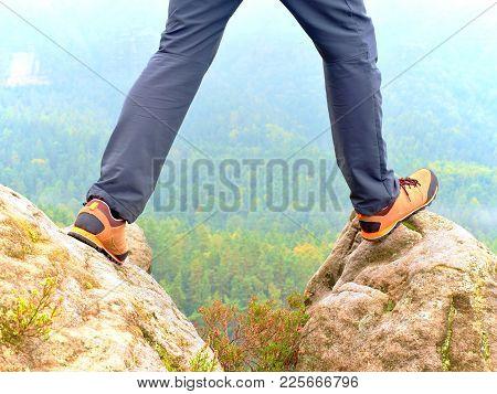 Hiker Legs In Comfortable Trekking  Boots Stand On Rocky Peak. Man Legs In Light Outdoor Trousers An
