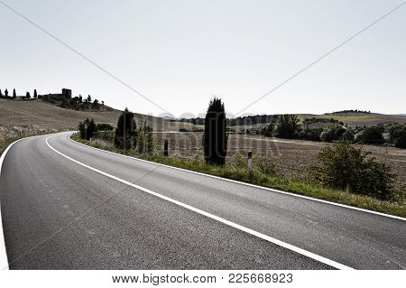 Stubble Fields On The Hills Of Tuscany. Tuscany Landscape After Harvest. Asphalt Road Between Plowed