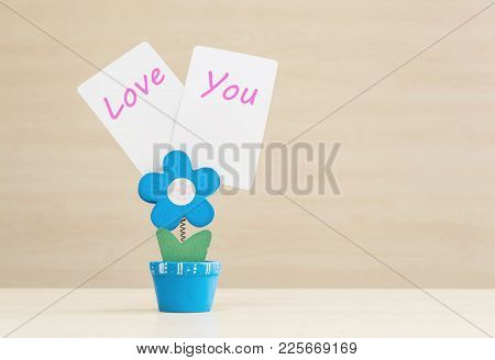 Closeup Clamp Photo In Blue Flower Shape Shape In Flowerpot With Love You Word On White Paper On Blu