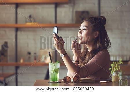 Beautiful Vietnamese Young Woman Applying Lip Gloss