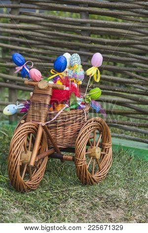 Easter Decoration Concept. Small Bicycle With Easter Eggs. Wicker Tricycle With Basket On Grass. Hap