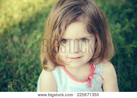 Girl With Brown Eyes On Cute Face Sitting On Green Grass On Sunny Summer Day. Childhood, Leisure And
