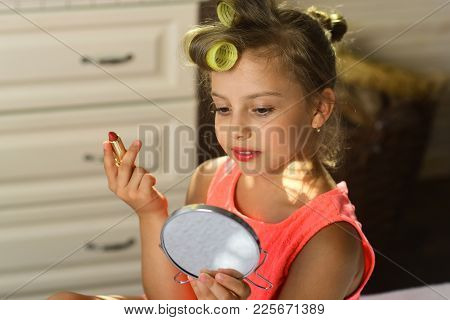 Little Girl With Curlers Wears Fashionable Dress Indoors. Beauty And Kids Makeup Concept. Kid With M