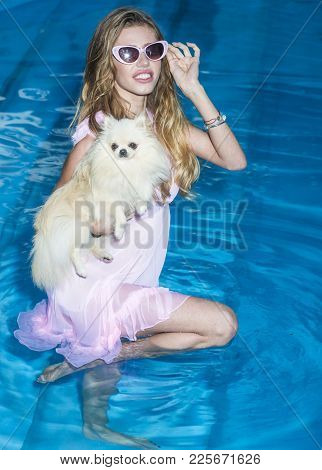 Girl With Small Dog In Swimming Pool. Sensual Woman With Cute Spitz Puppy In Blue Water. Pet, Compan