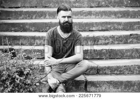 Handsome Young Stylish Hipster Man With Long Beard In Grey Shirt Sitting Outdoor On Stony Stairs Wit