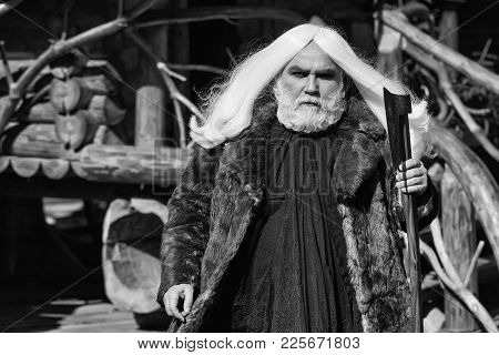 Brutal Druid Old Man With Long Silver Hair And Beard In Fur Coat With Axe In Hand On Log House Backg