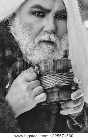 Druid Old Man With Wrinkles Long Silver Beard And Hair With Wooden Mug In Hands On Blurred Backgroun