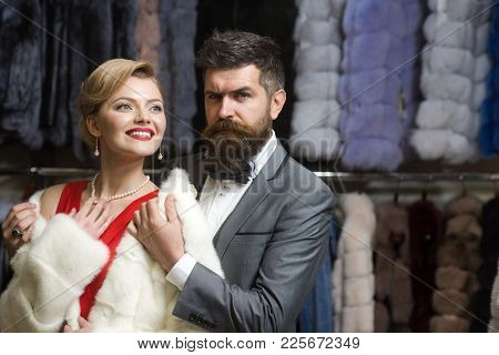 Rich Fashion Concept. Customer With Beard And Woman Buy Furry Coat. Man And Girl With Happy Faces Ho