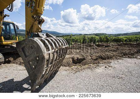 Excavator Bucket On The Asphalt Road Near The Vineyard. Excavator In Construction Site On The Italia