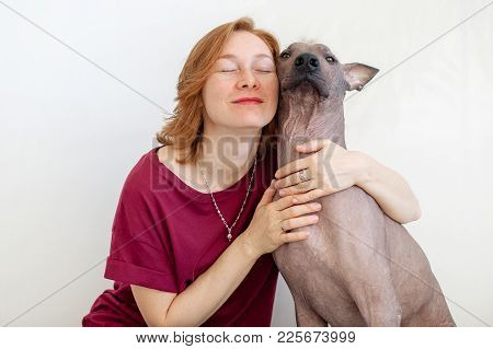 A Woman With Eyes Closed Hugging With A Mexican Hairless Dog