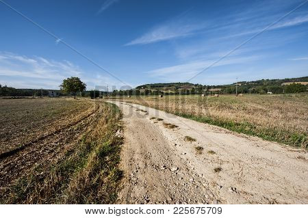 Plowed Sloping Hills Of Tuscany In The Autumn. Rural Landscape With Field After Harvest.