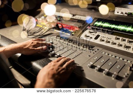 music, technology, people and equipment concept - man using mixing console in sound recording studio over festive lights