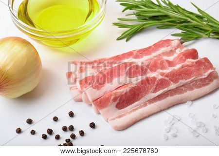 Raw bacon slices with condiments on white background