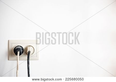 Electric Socket With Two Stuck Electric Plugs On A White Wall. Power Socket And Plug