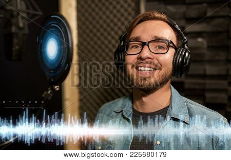 music, show business, people and technology concept - male singer with headphones and microphone singing song at sound recording studio