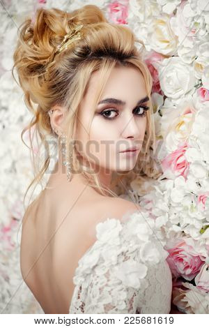 Close-up portrait of a beautiful bride woman posing by background of roses. Wedding make-up and hairstyle. Jewellery.