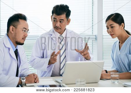 Vietnamese Doctor Conducting Meeting With Coworkers In His Office