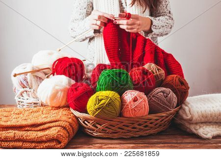 The Woman That Hold Needles And Knitting A Red Warm Jacket On The Market. Hobby Concept Of Knit