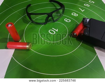 Image Of Shooting Gallery With Target, Glasses, Gun On Brown Table