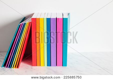 Colorful Books Are Outlined In The Colors Of The Rainbow. Stacked Of The Books On A Shelf Near The W