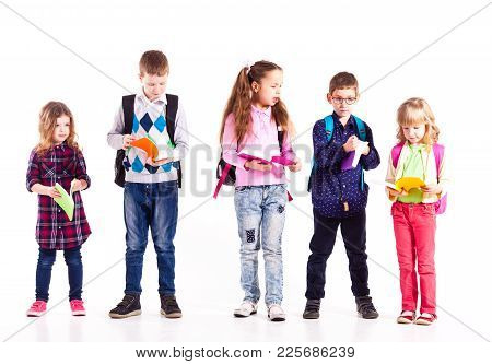 Pupils With Backpacks Holding Books In The Hands Are Ready To Go To School. Back To School Concept