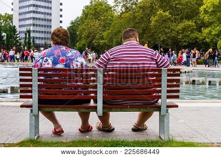 Debrecen, Hungary - August 20, 2017: Obese People Rest On A Bench Near The Fountain In The Park Afte